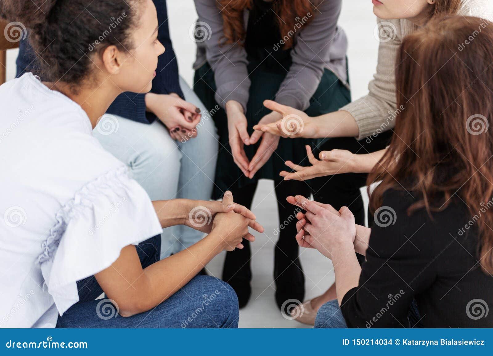 Gruppe junge Frauen, die Sitzen in einem Kreis sprechen Psychologisches St?tzkonzept
