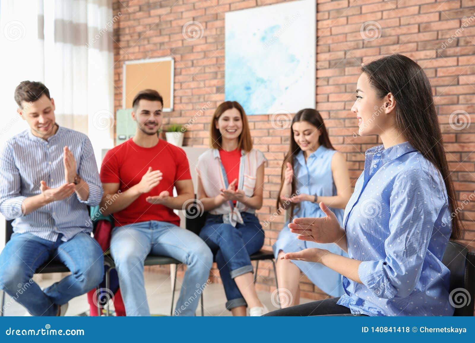 Gruppe junge Leute, die Gebärdensprache mit Lehrer lernen
