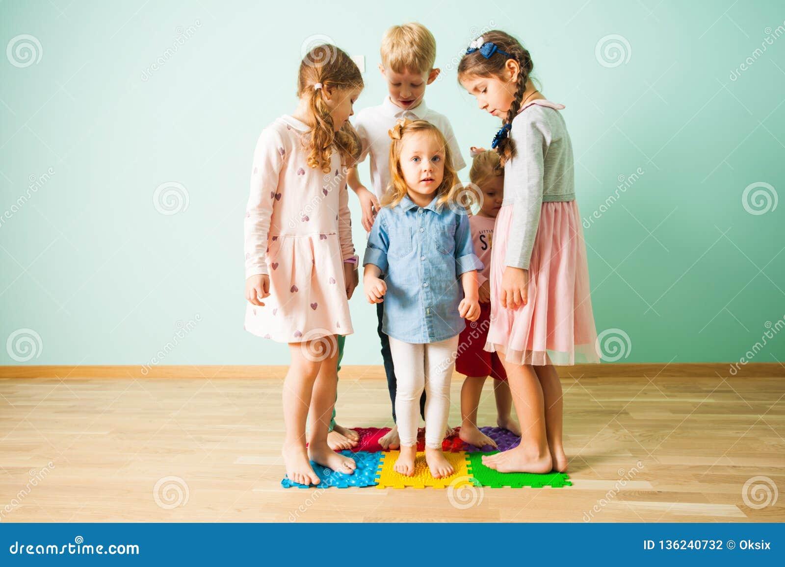 Gruppe Kinderstände auf dem Massieren von Matten