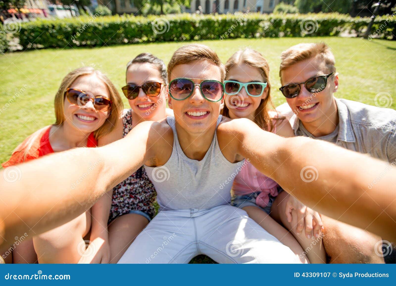 Gruppe lächelnde Freunde, die selfie im Park machen