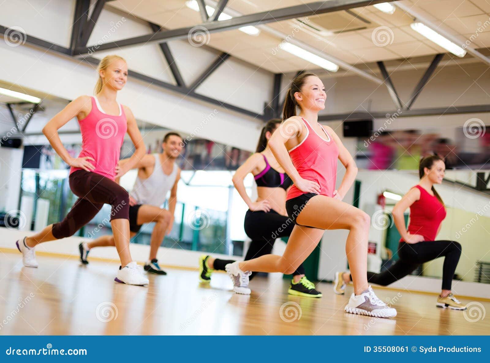 Gruppe lächelnde Leute, die in der Turnhalle trainieren