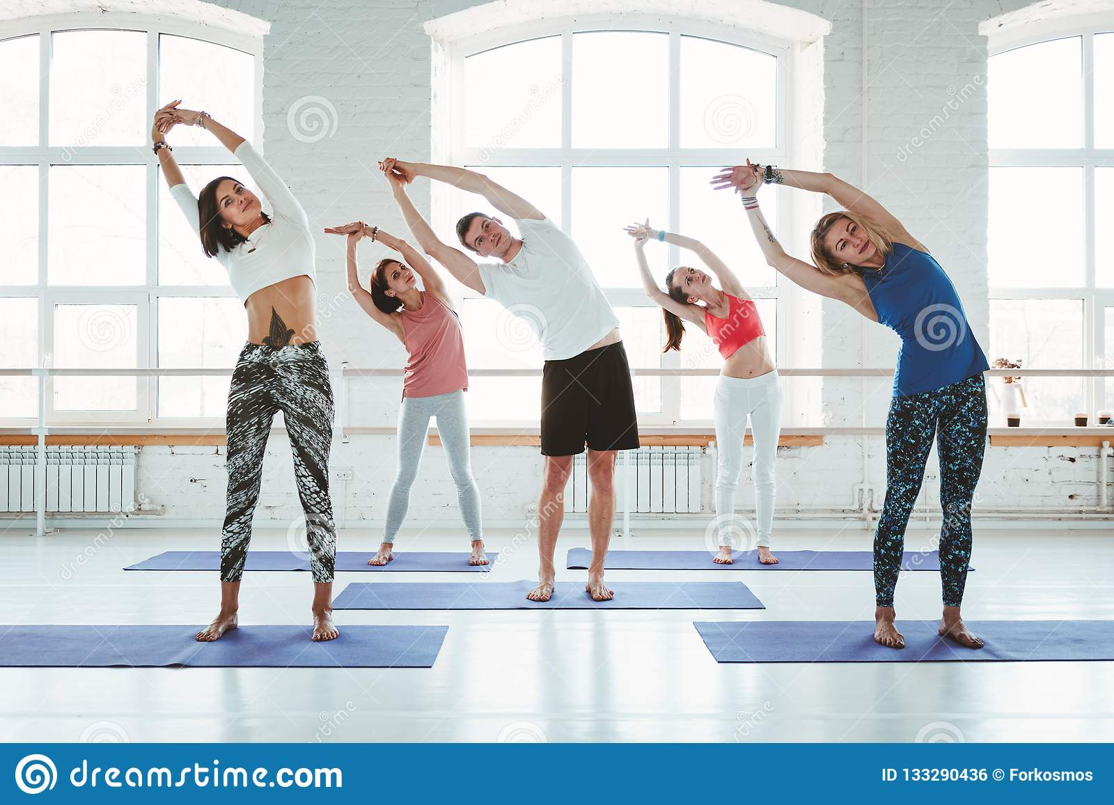 Gruppe Männer und Frauen, die Eignungstraining in der Klasse aufwärmen und tun Junge aktive Leute tun Yoga zusammen