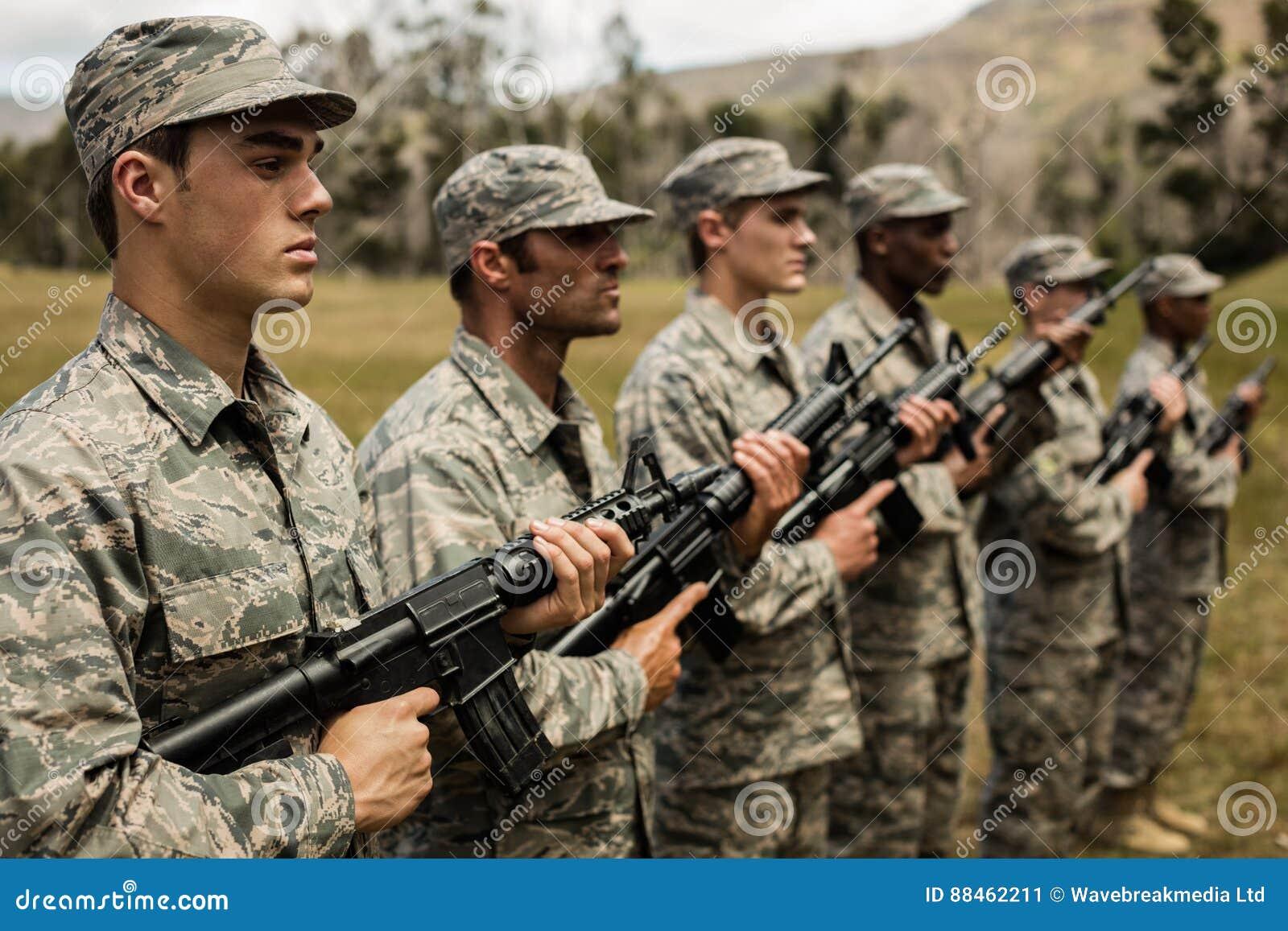 Gruppe Militärsoldaten, die mit Gewehren stehen