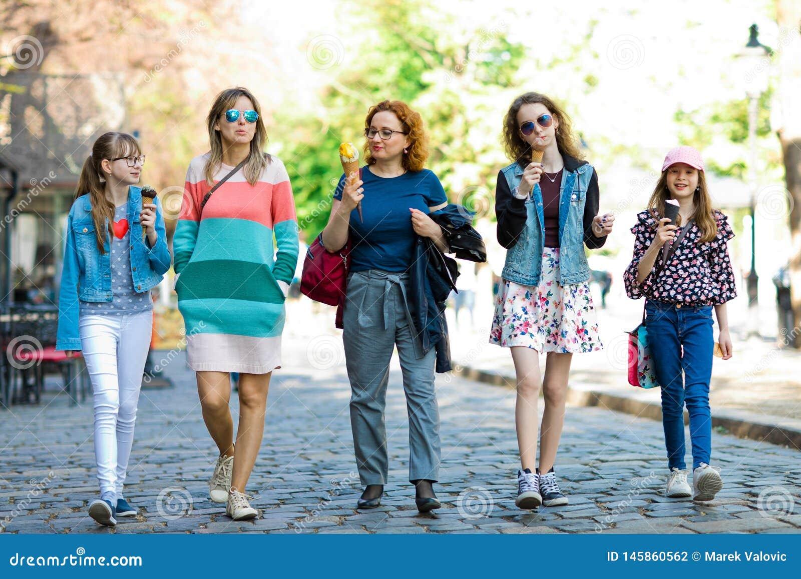 Gruppe Modemädchen, die durch im Stadtzentrum gelegenes - Eis cre haben gehen