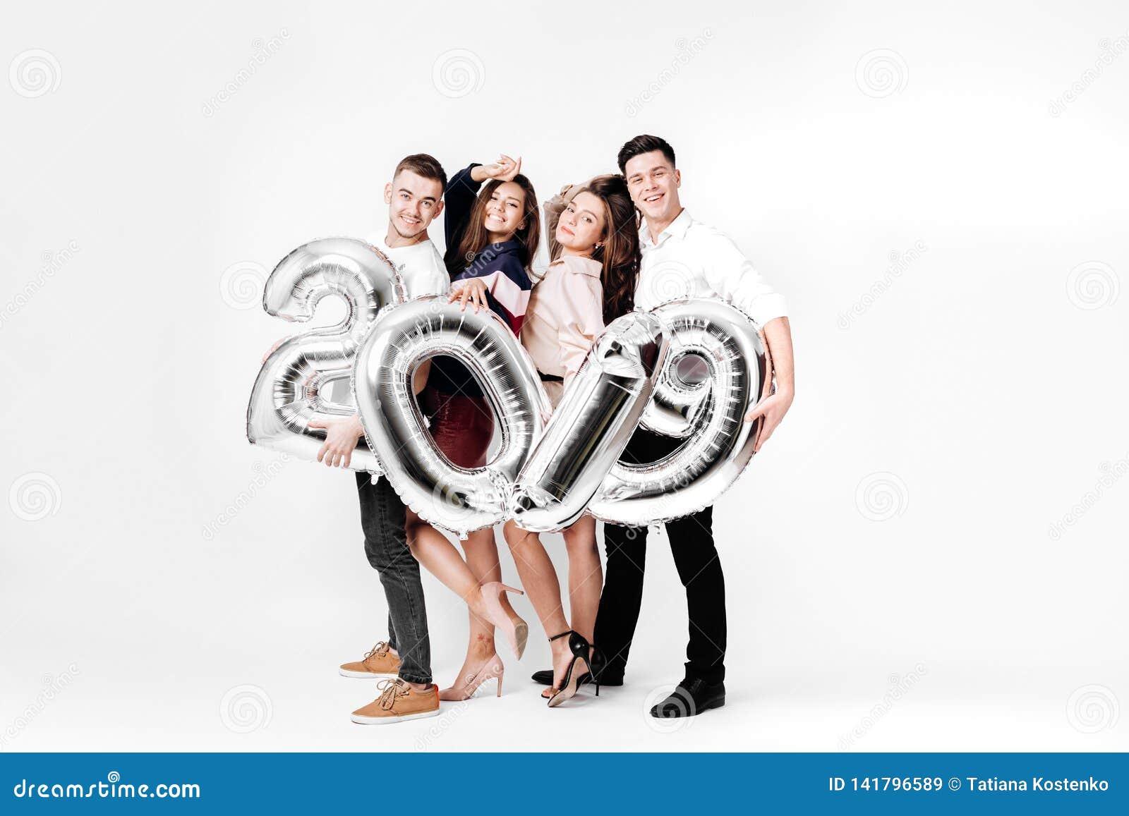 Gruppe nette Freunde von zwei Mädchen und zwei Kerle, die in der stilvollen Kleidung gekleidet werden, halten Ballone in Form