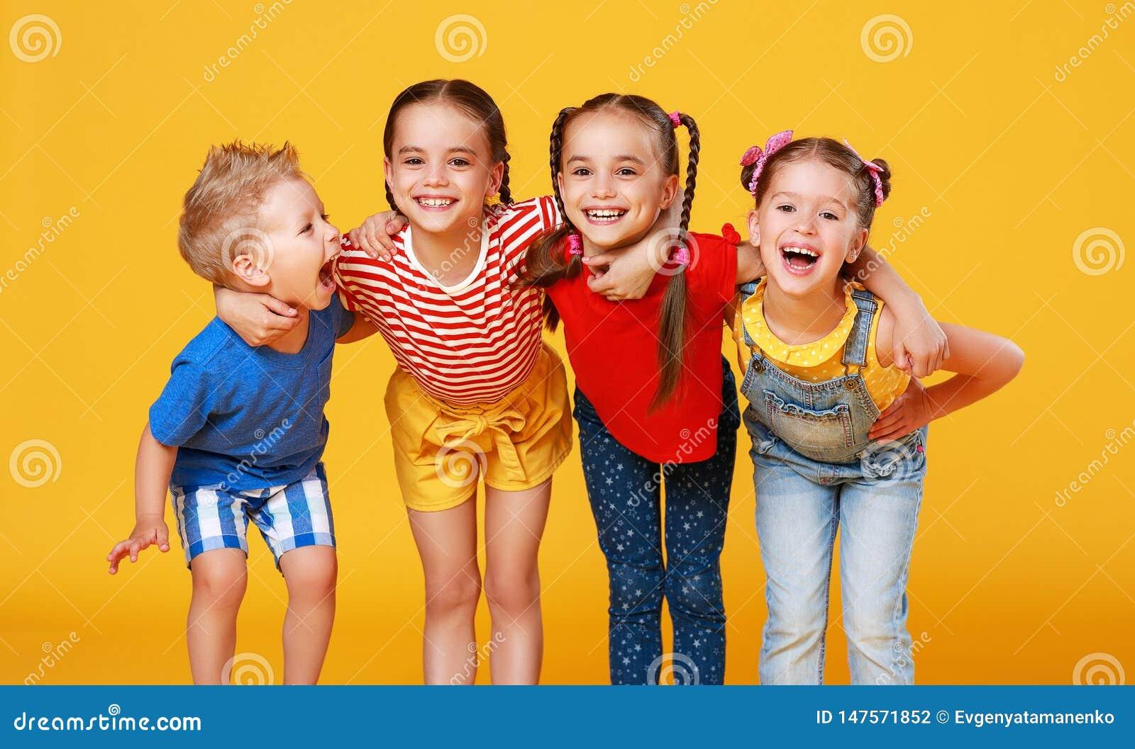 Gruppe nette gl?ckliche Kinder auf farbigem gelbem Hintergrund