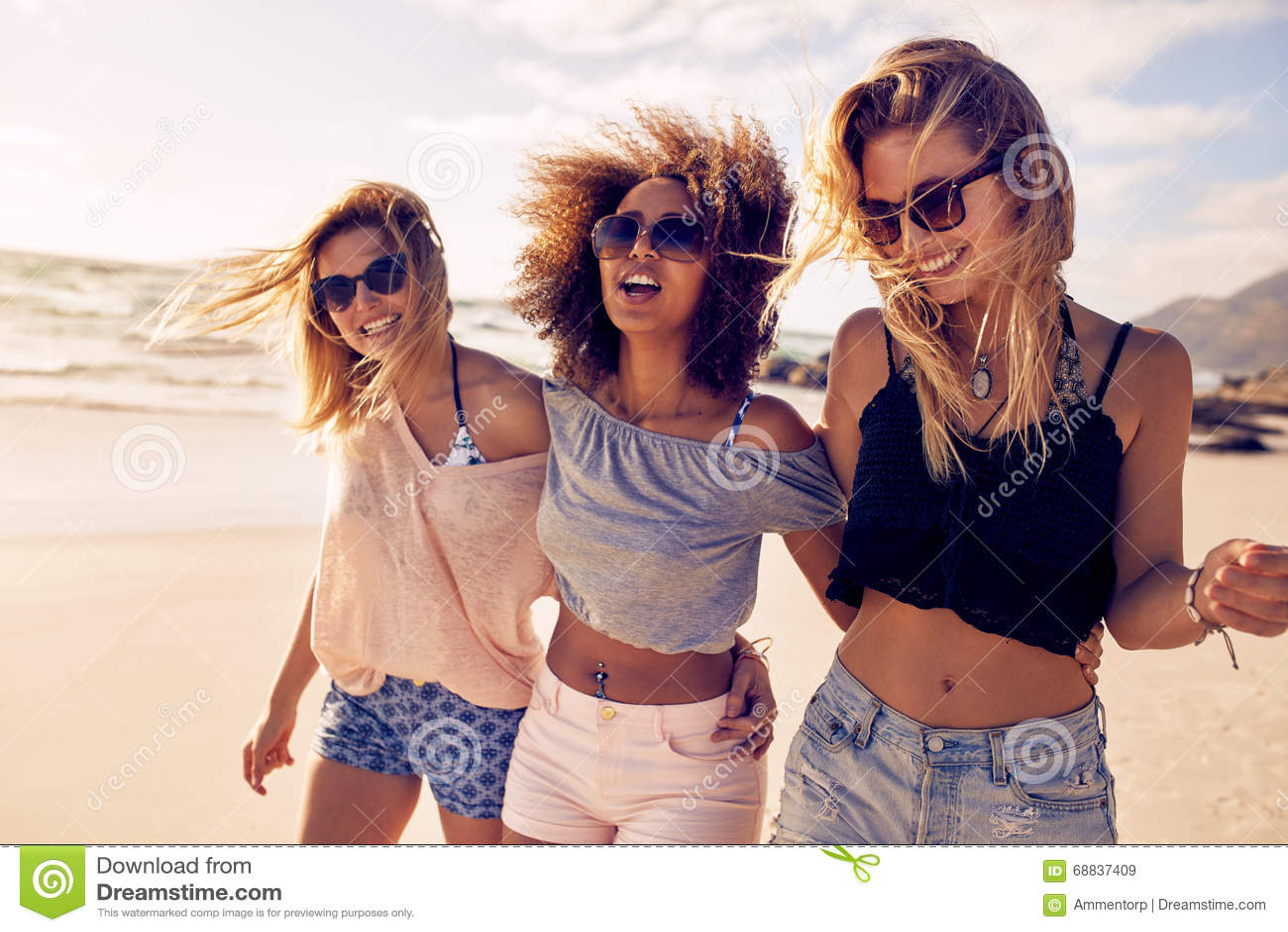 Gruppe schöne junge Frauen, die auf einen Strand schlendern
