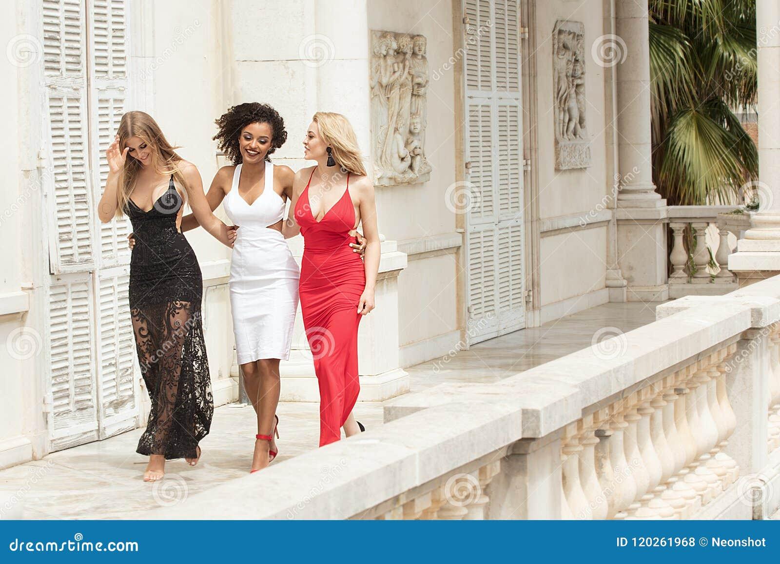 Gruppe schöne sexy Damen in den eleganten Kleidern am sonnigen summe