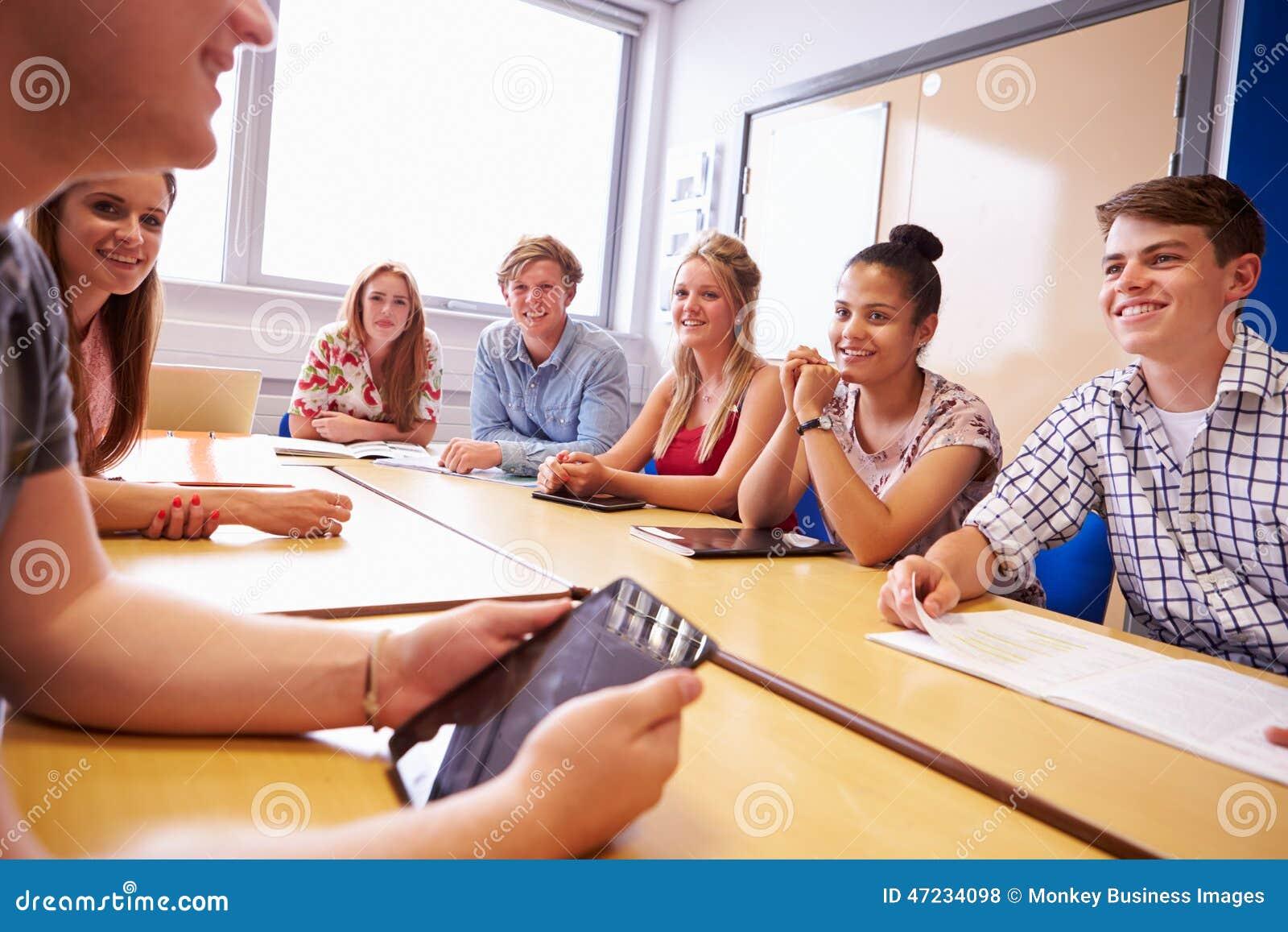 Gruppe Studenten, die bei Tisch sitzen, Diskussion habend