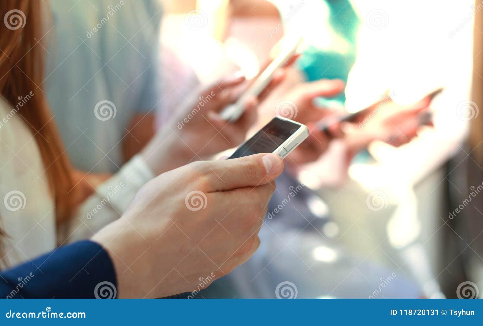 Gruppe Studenten, die Smartphones aufpassen Sucht der jungen Leute zu den Tendenzen der neuen Technologie
