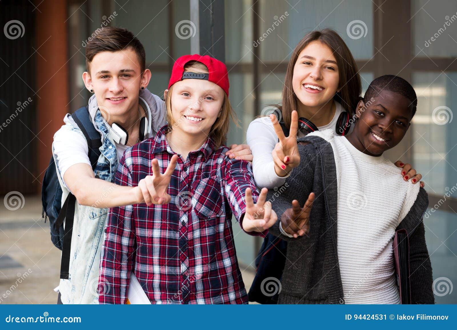 Gruppe Teenager, der äußere Schule aufwirft