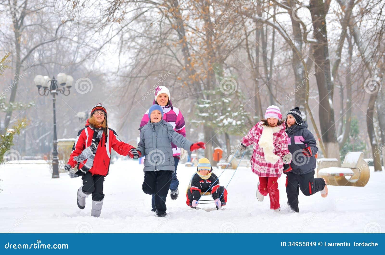 Gruppe von den Kindern und von Mutter, die auf Schnee in der Winterzeit spielen