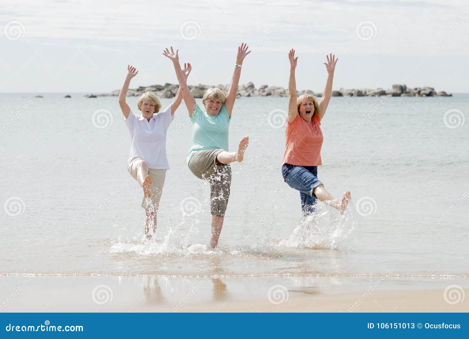 Gruppe von drei älteren reifen Frauen im Ruhestand auf ihrem 60s, das Spaß das glückliche Gehen auf dem Strandlächeln zusammen ge