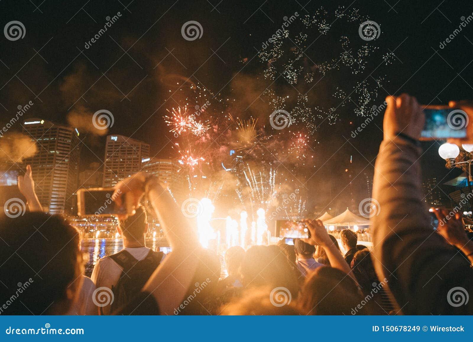 Gruppe von Personen, die helle funkende Feuerwerke an einem Festival genießt