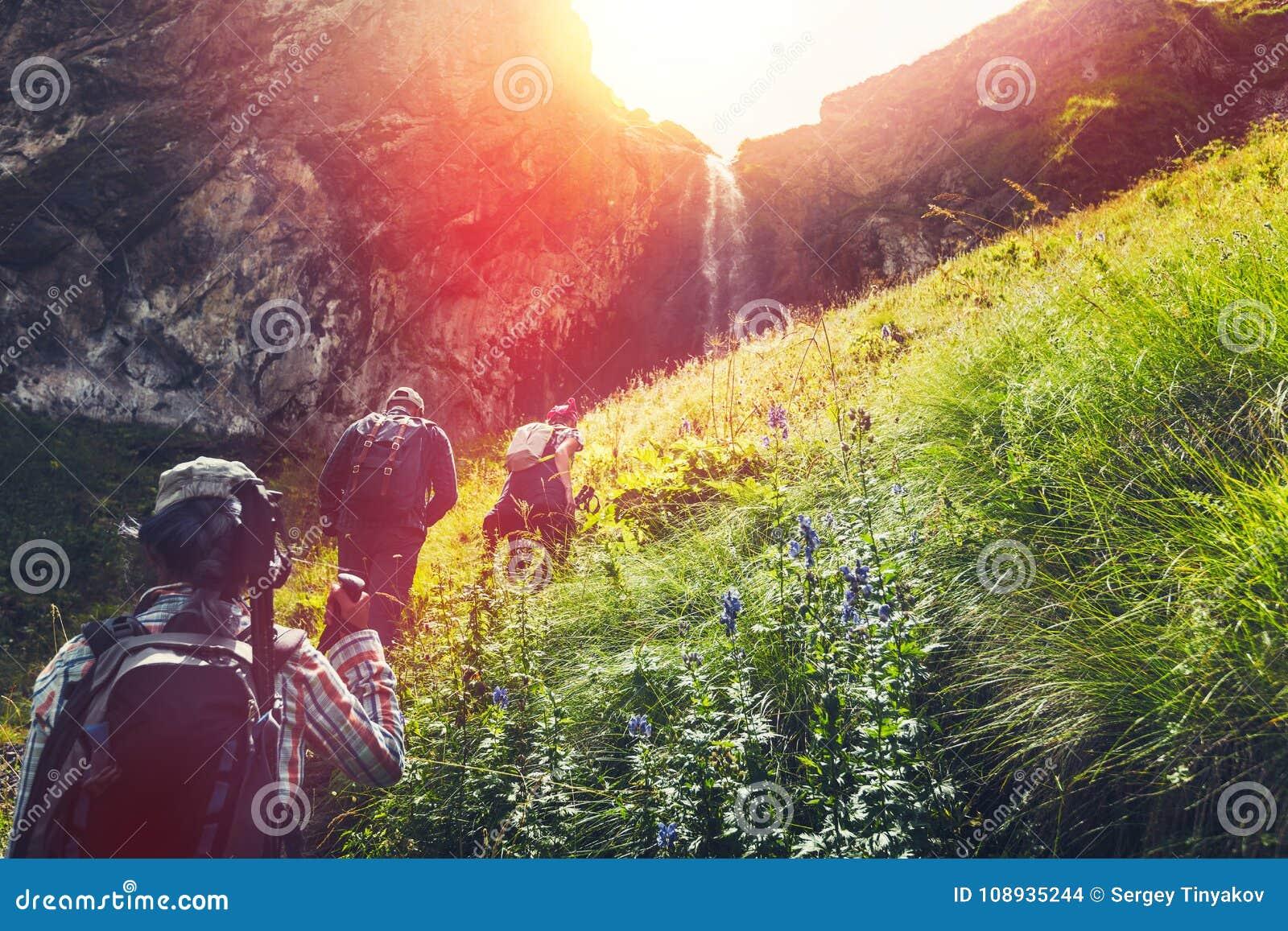 Gruppe Wanderer-Touristen, die aufwärts zum Wasserfall gehen Reise-Abenteuer-Konzept im Freien