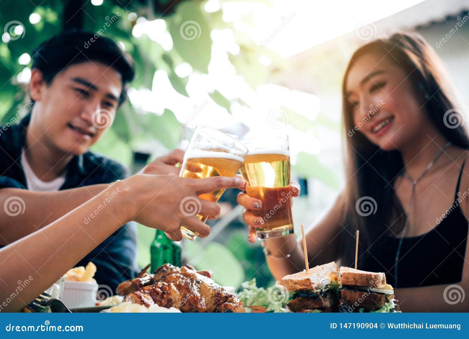 Gruppe zujubelndes Bier der asiatischen Leute an der gl?cklichen Stunde des Restaurants im Restaurant