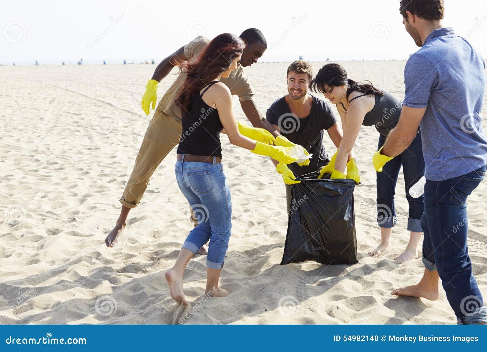 Gruppen av att ordna för volontärer rackar ner på på stranden