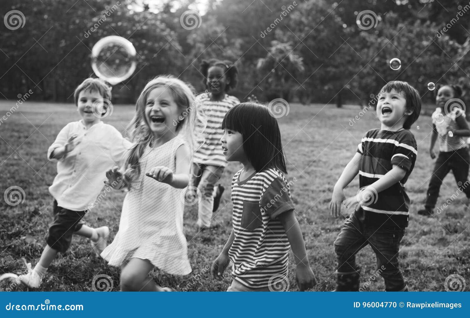 Gruppen av dagisungevänner som spelar att blåsa, bubblar gyckel