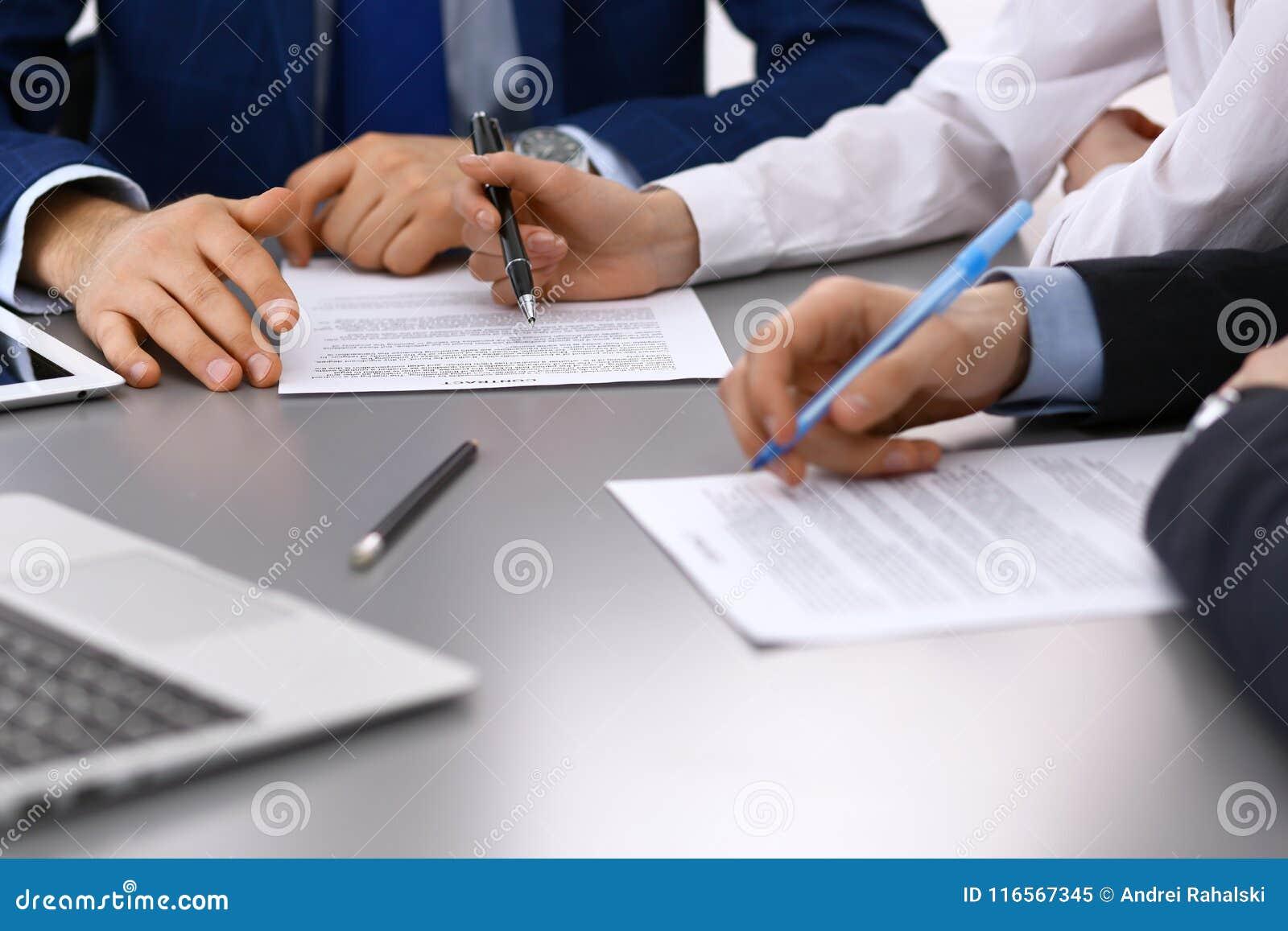 Gruppen av den affärsfolk och advokaten som diskuterar avtalet, skyler över brister sammanträde på tabellen, closeup Affärsmannen