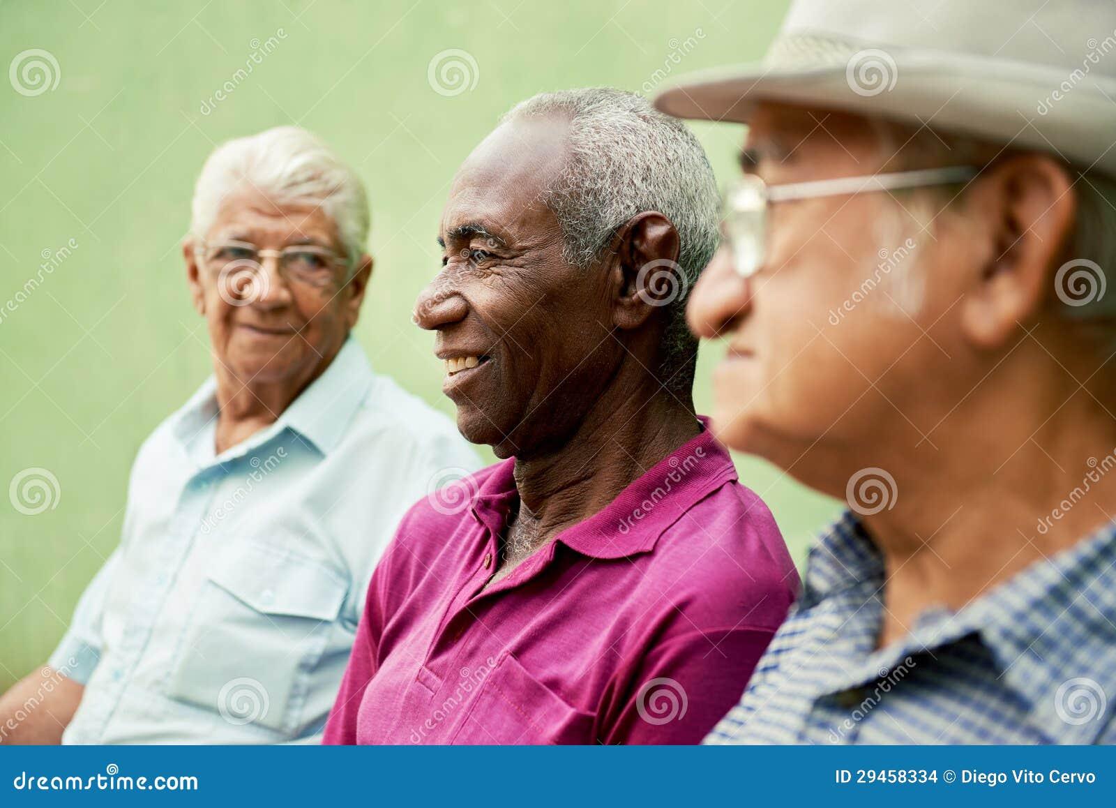 Gruppen av gammala svart och caucasian manar som in talar, parkerar