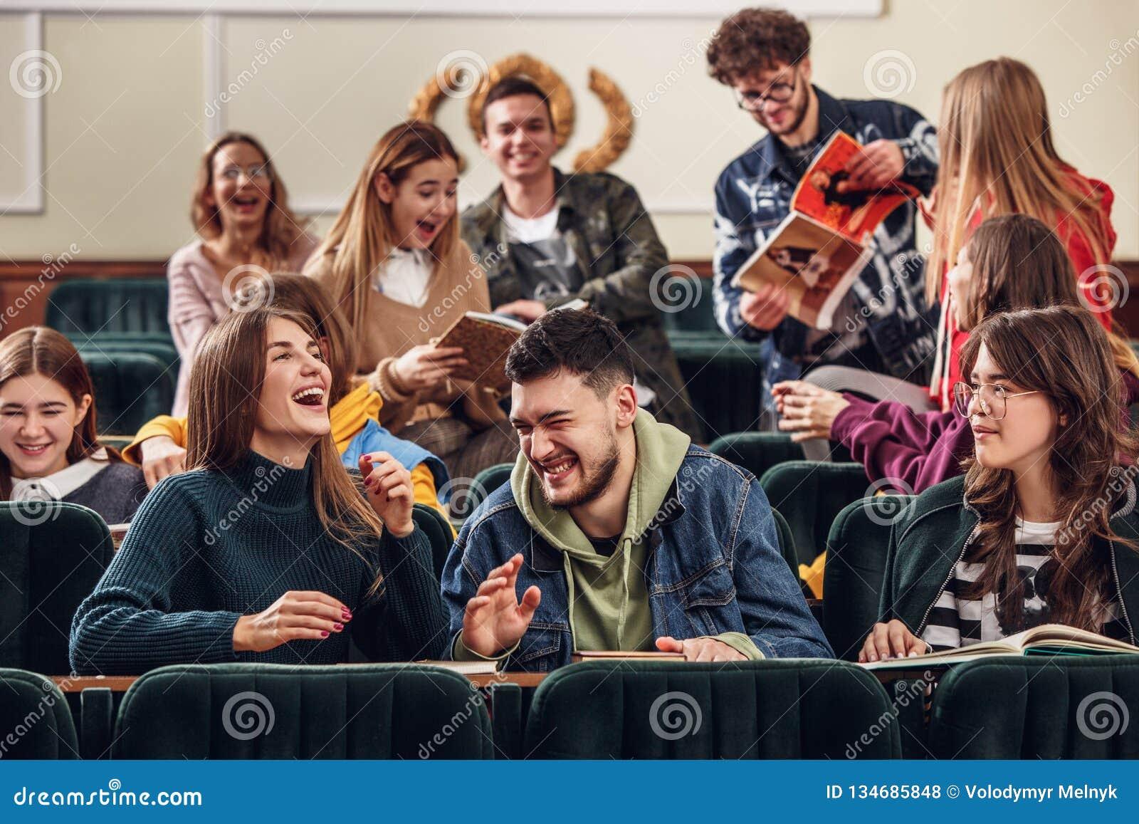 Gruppen av gladlynta lyckliga studenter som sitter i en hörsal för kurs