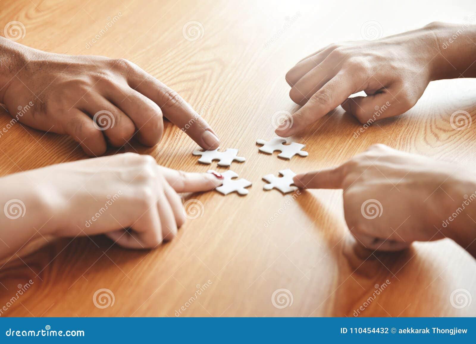 Gruppen av händer för affärsfolk rymmer pusslet