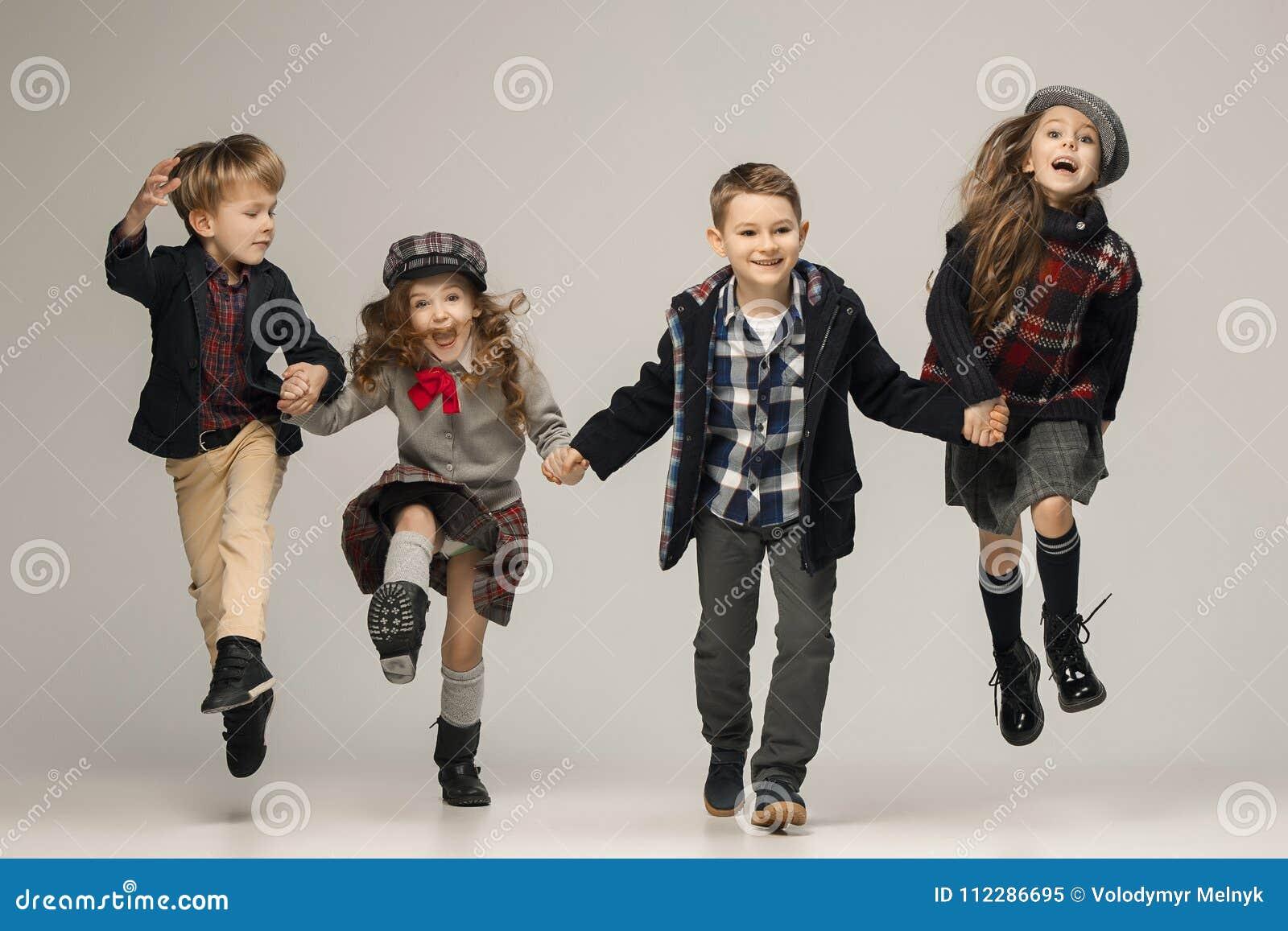 Gruppen av härliga flickor och pojkar på en pastellfärgad bakgrund