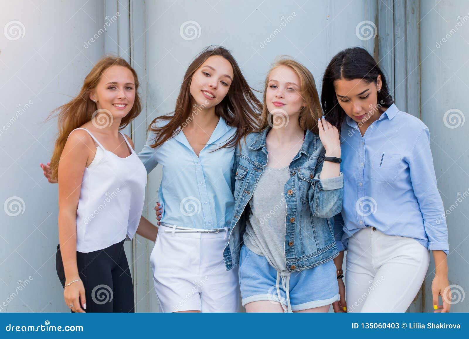 Gruppen av kvinnliga studenter i sommar beklär att posera tillsammans utomhus- och att se kameran Modestående av den unga student