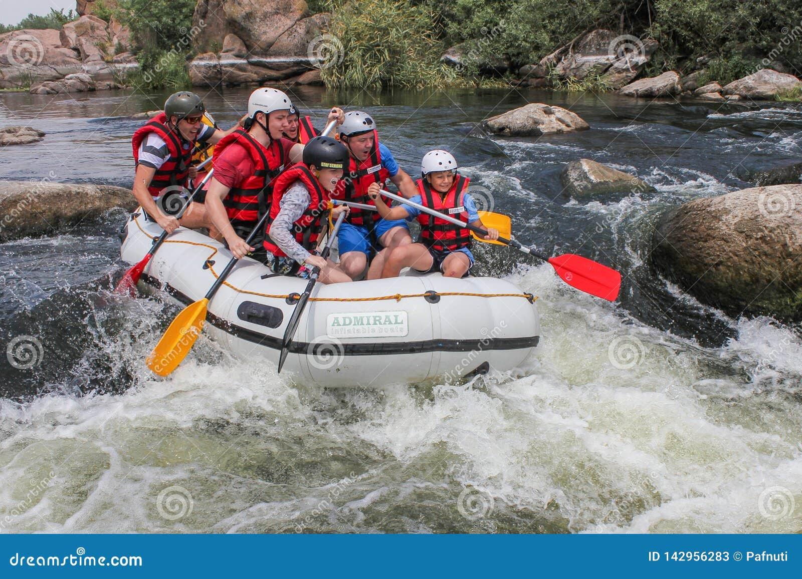 Gruppen av män och kvinnor, tycker om vatten som rafting på floden
