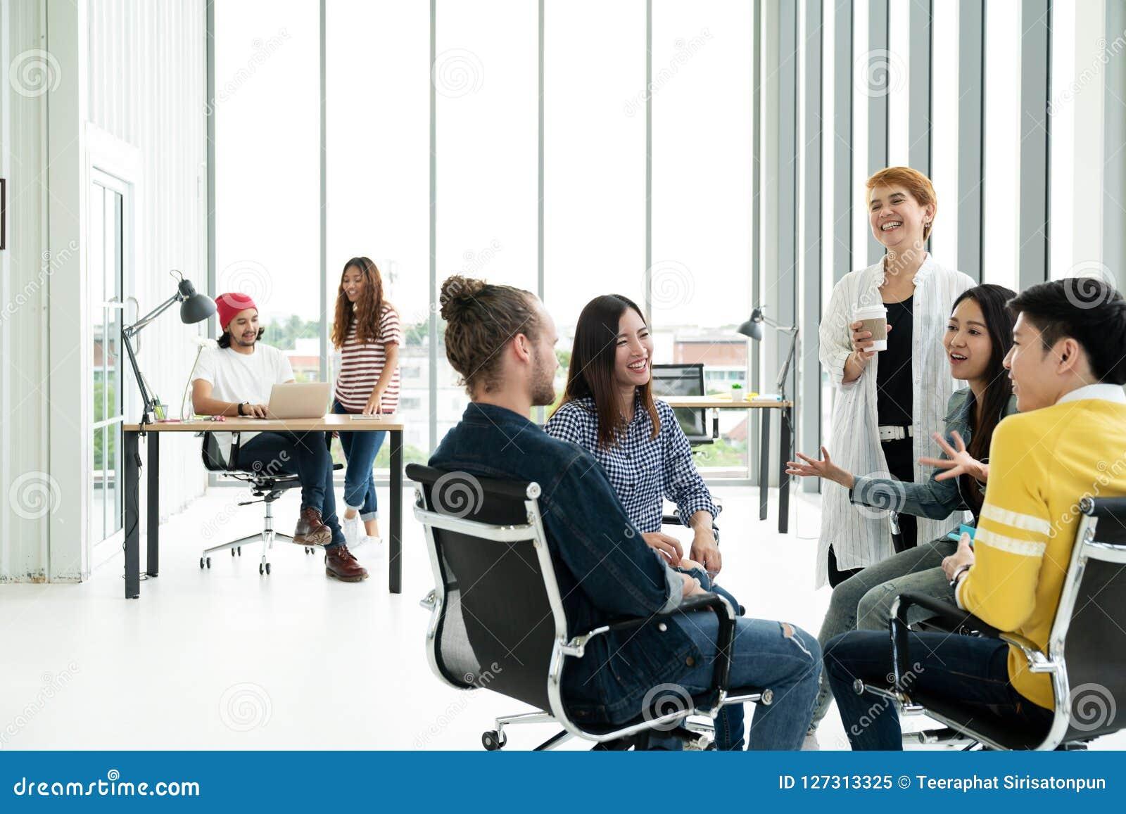 Gruppen av mångfaldfolk Team att le och att skratta och gladlynt i litet möte på det moderna kontoret