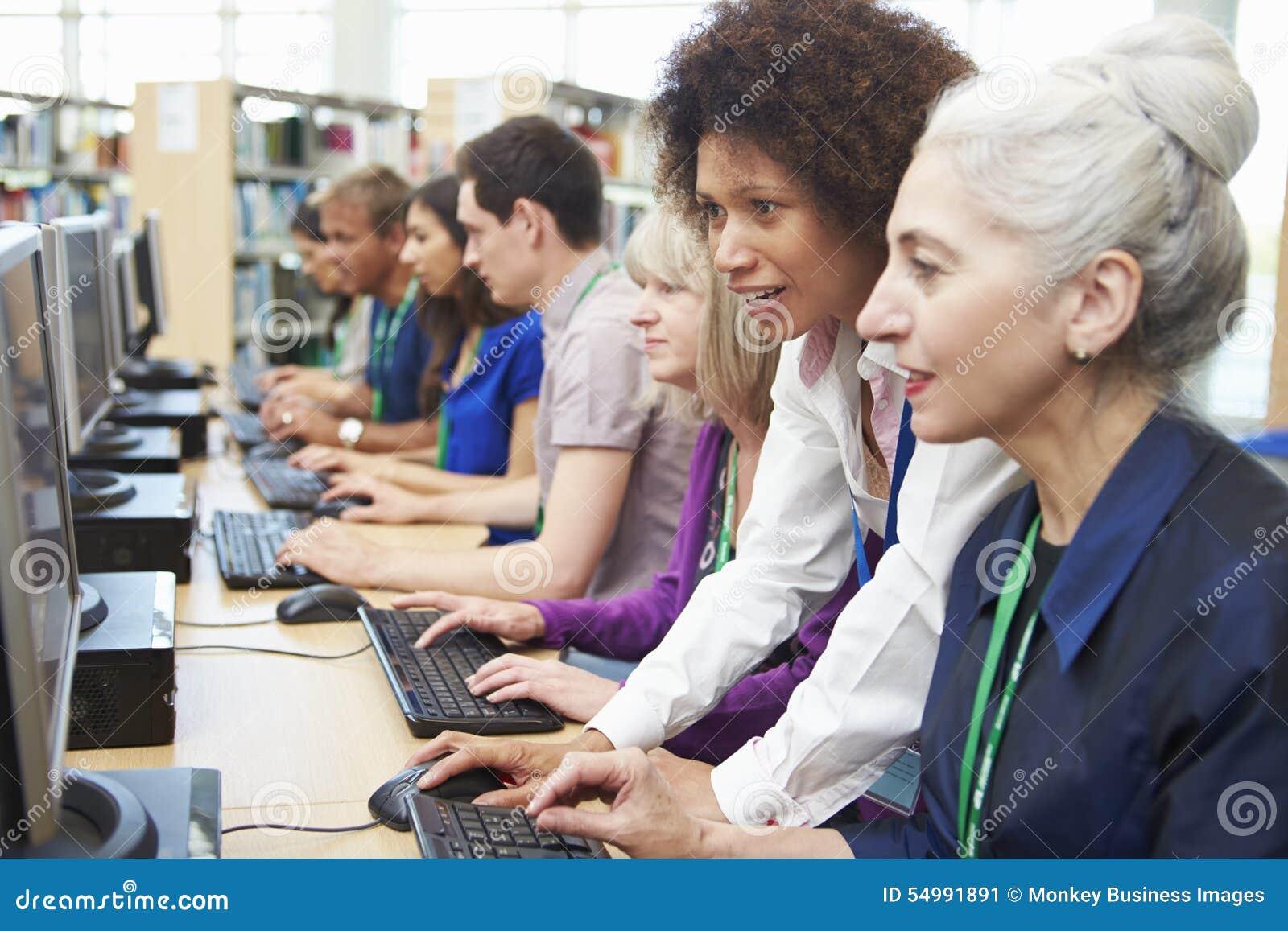 Gruppen av mogna studenter som arbetar på datorer med, handleder