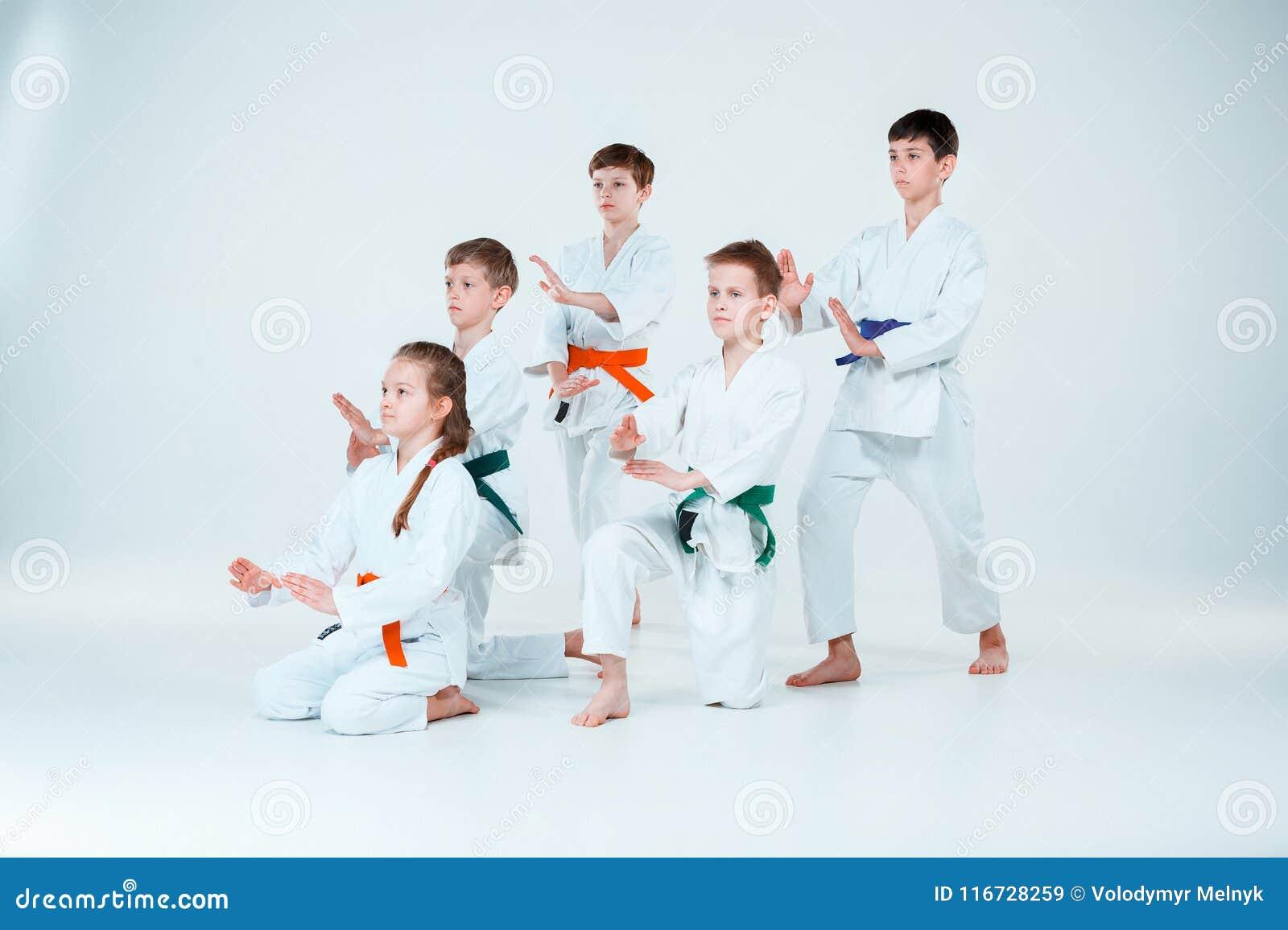 Gruppen av pojkar och flickastridighet på Aikidoutbildning i kampsportskola Sund livsstil och sportbegrepp