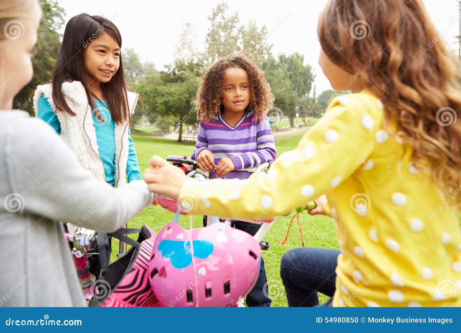 Gruppen av unga flickor med cyklar parkerar in