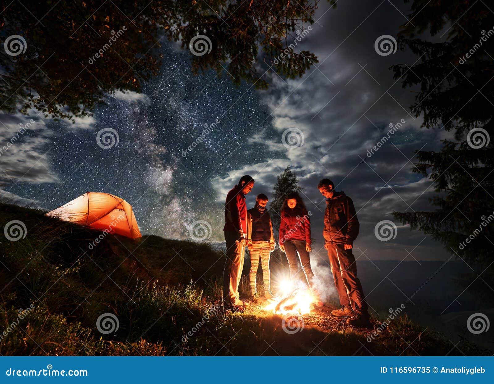 Gruppen av unga turister står runt om branden nära tältet under den molniga himlen med den mjölkaktiga vägen