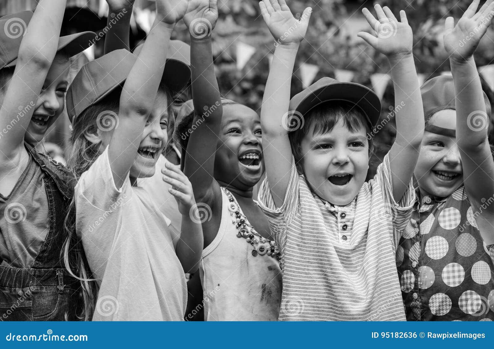 Gruppen av ungar skolar fältturer som utomhus lär aktiv smilin