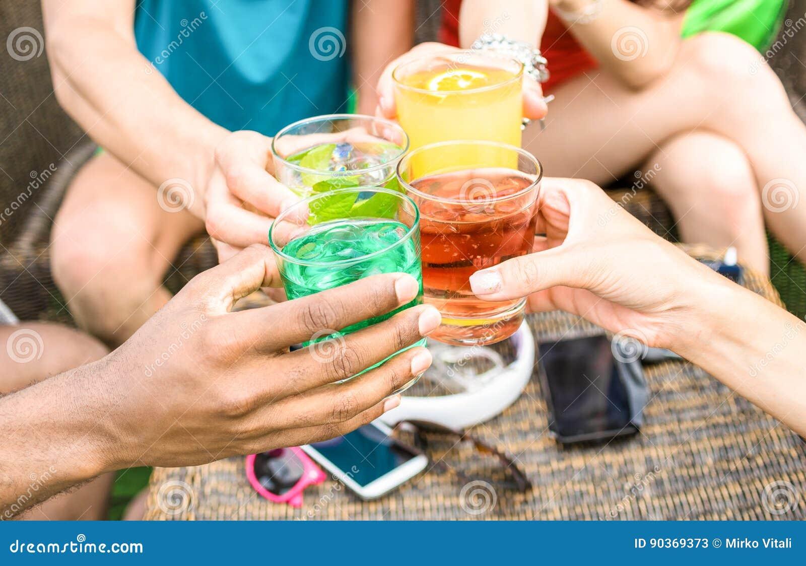 Gruppen av vänner räcker att dricka sommarcoctailar på strandstången