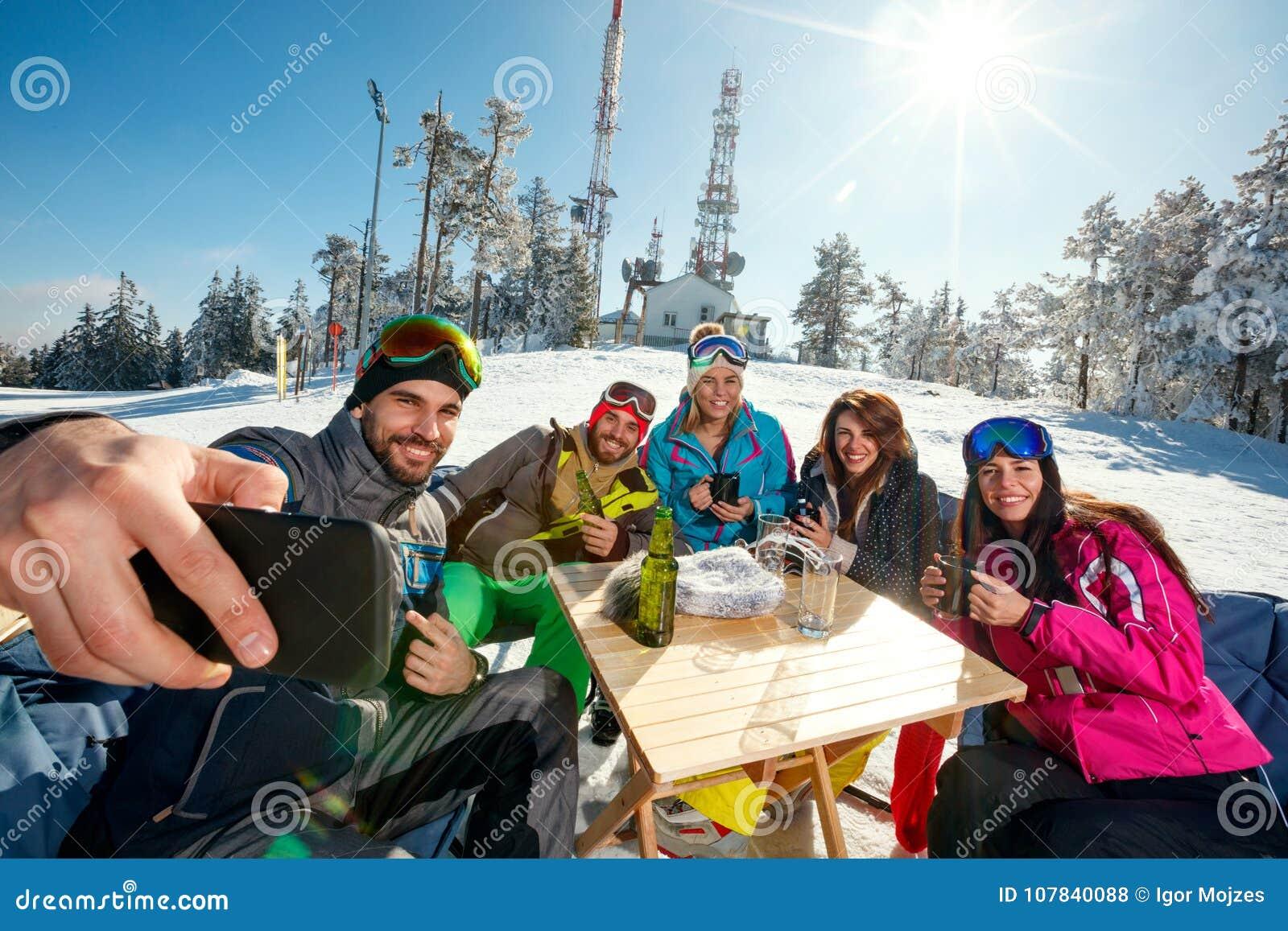 Gruppen av vänner som skrattar och tycker om i drink på, skidar semesterorten