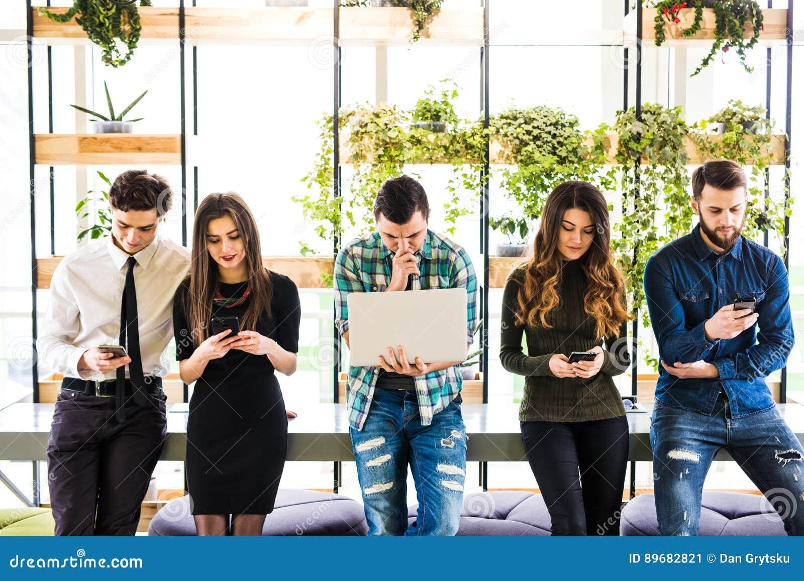 Gruppen av vänner som står på tabellen och alla, använder hans divices i modernt kontorsrum Tillsammans gyckel i apparat