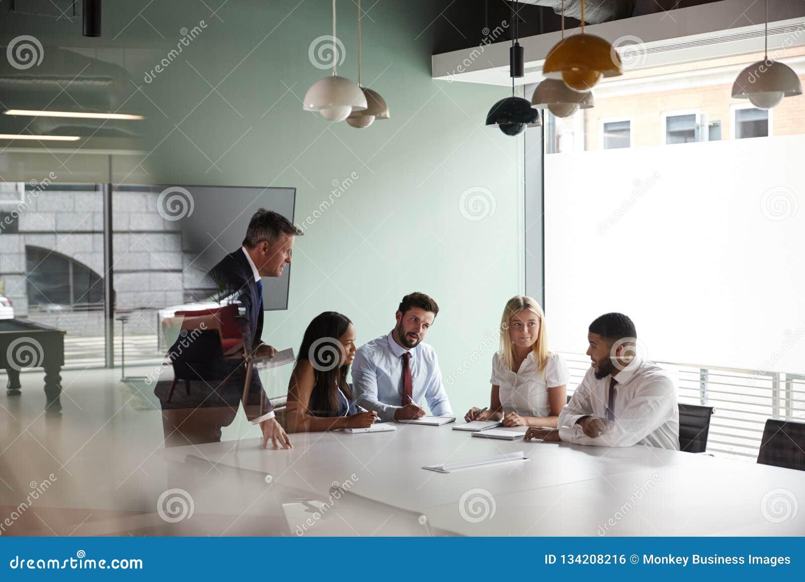 Gruppen-Sitzung um Tabelle am graduierten Einstellungs-Einschätzungs-Tag und Zusammenarbeiten auf Aufgabe, während, beobachtend d