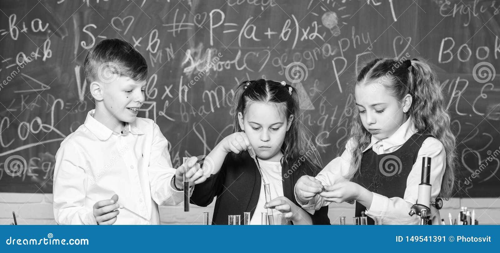 Gruppenschulsch?ler studieren chemische Fl?ssigkeiten Schullabor M?dchen und Jungenf?hrungsexperiment mit Fl?ssigkeiten teamwork