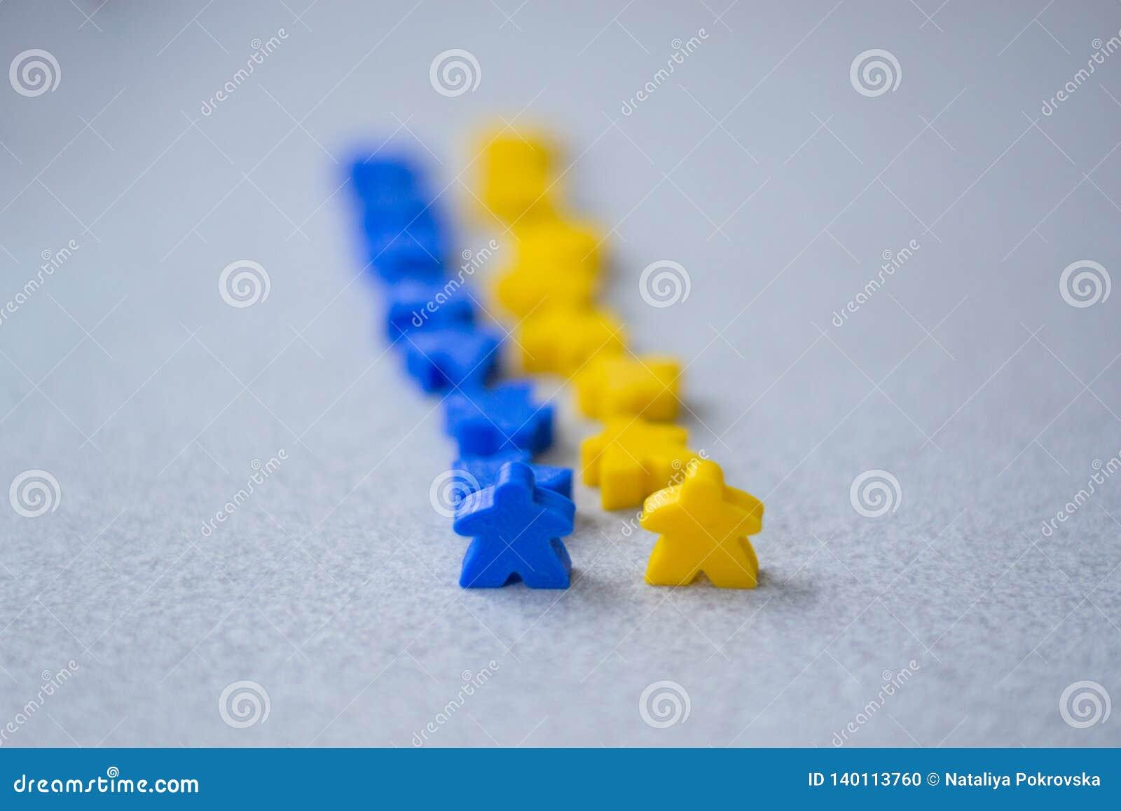 Grupper av färgrika meeples av två lag Färger av den gul ukrainska flaggan - som är blå och Små diagram av mannen
