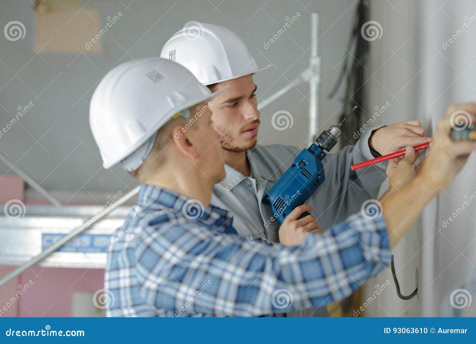 Gruppera byggmästare i hardhats med den elektriska drillborren inomhus