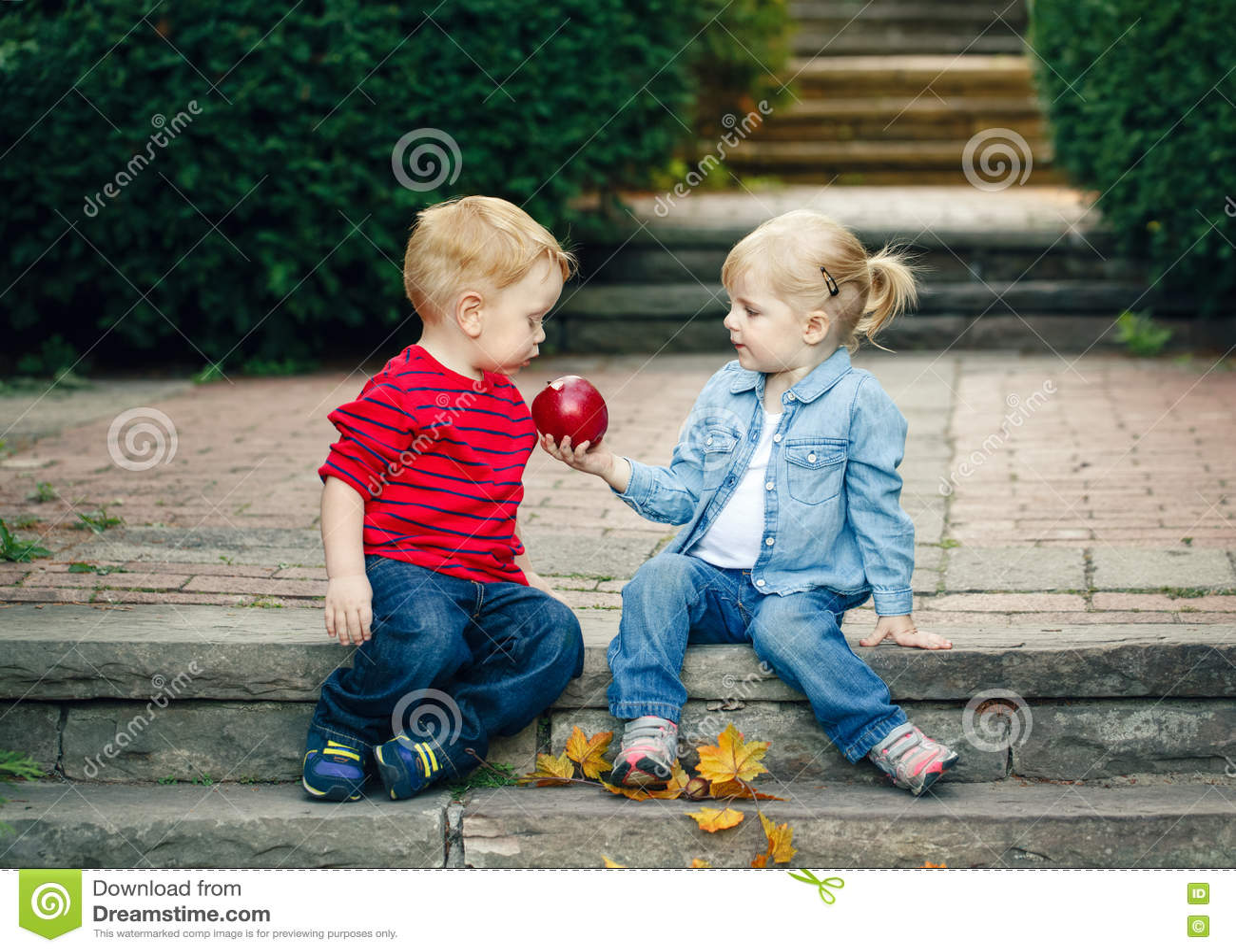 Gruppera ståenden av två vita Caucasian gulliga förtjusande roliga barnsmå barn som sitter dela tillsammans äpplemat