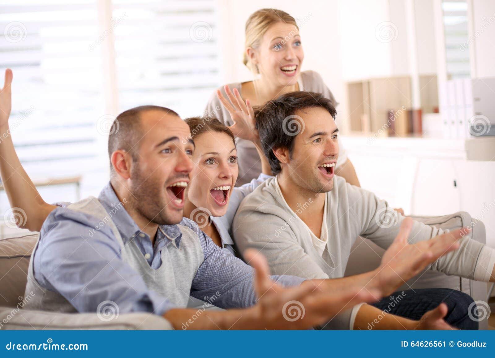Gruppo allegro di amici che guardano la partita di calcio