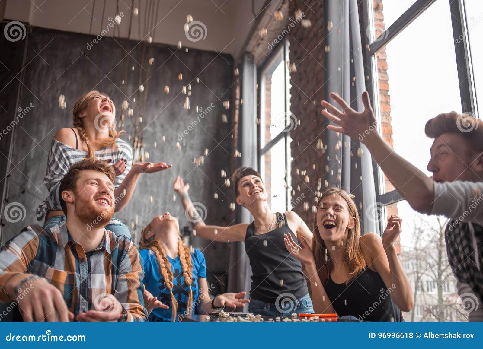 Gruppo allegro di amici divertendosi a casa, mangiando popcorn e godendo insieme