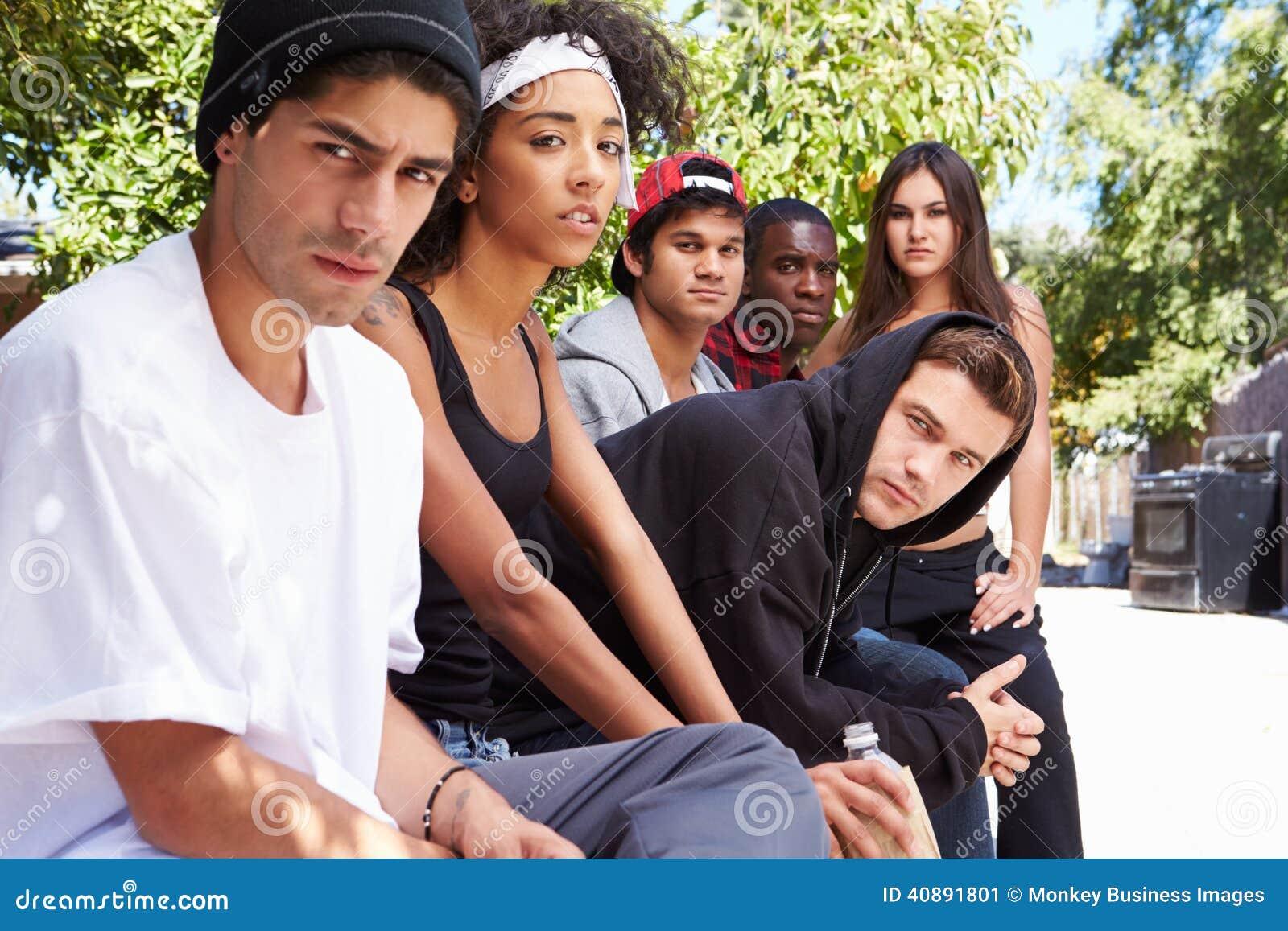 Gruppo dei giovani nell ambiente urbano che si siede sul banco