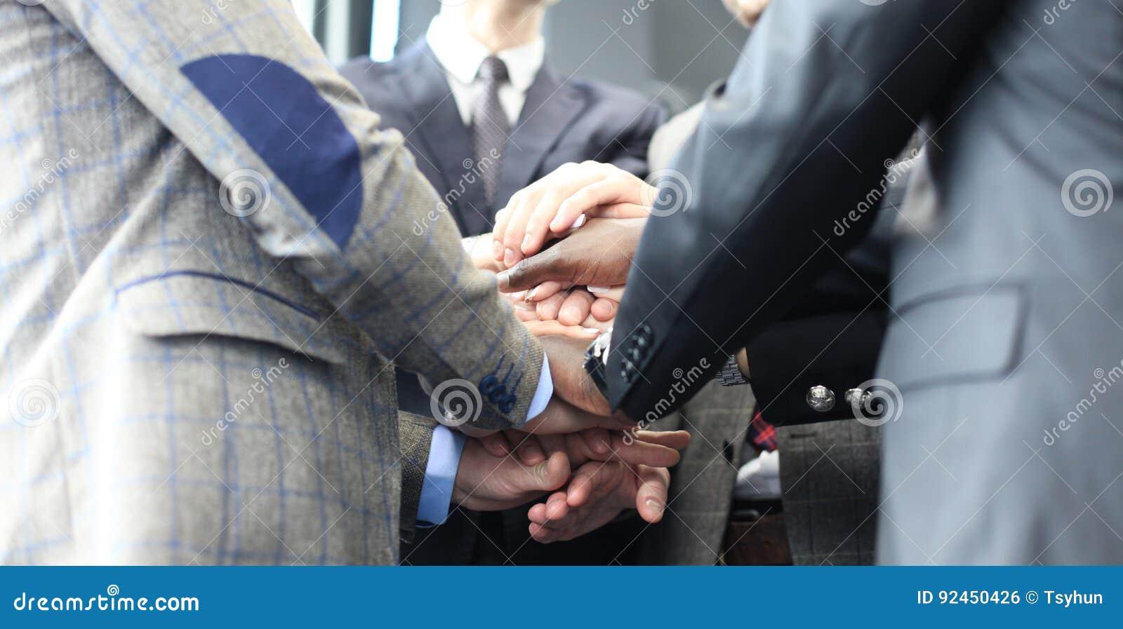 Gruppo dell uomo d affari in mani commoventi del vestito insieme Fuoco selettivo