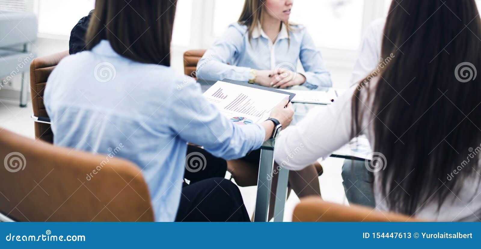 Gruppo di affari ad una conferenza di funzionamento che si siede ad uno scrittorio e che discute le edizioni importanti