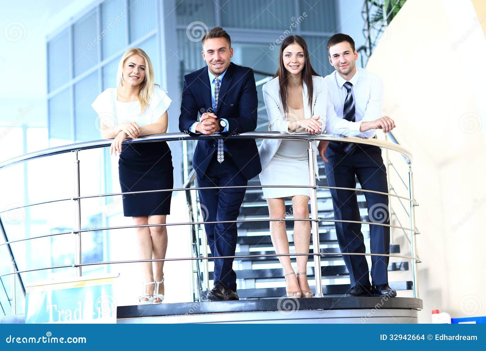 Gruppo di affari positivo che sta sulle scale dell ufficio moderno