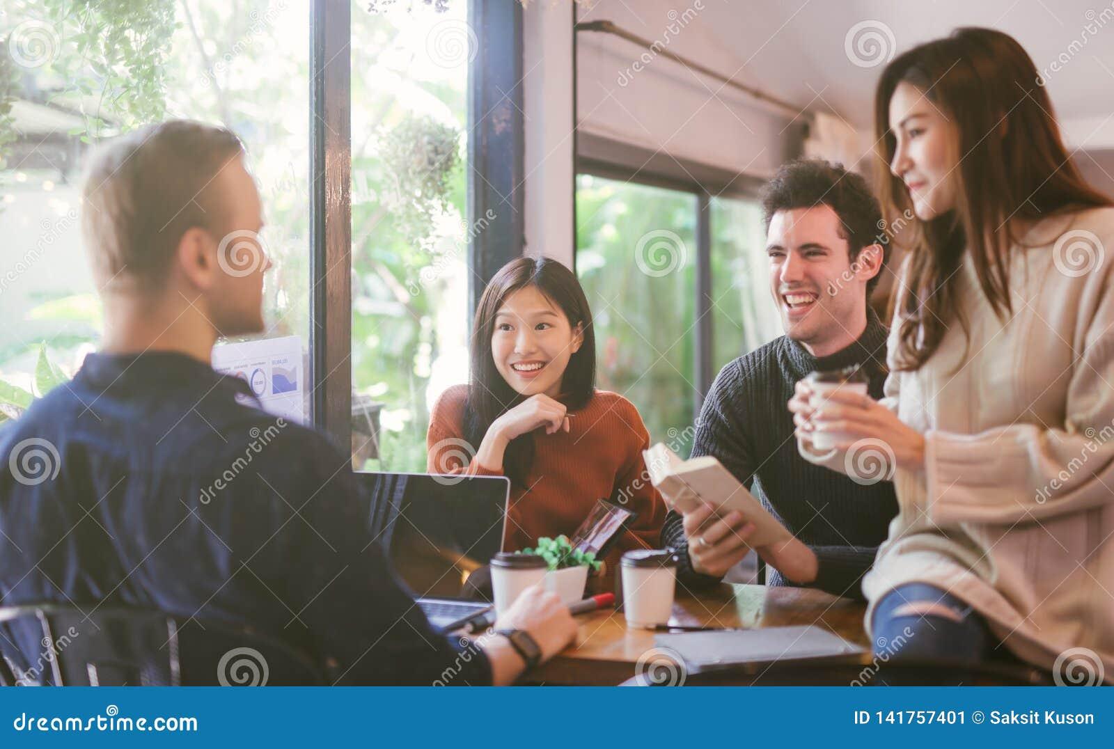 Gruppo di amici che chiacchierano e che utilizzano computer portatile nel caffè al caffè della caffetteria in università che parl